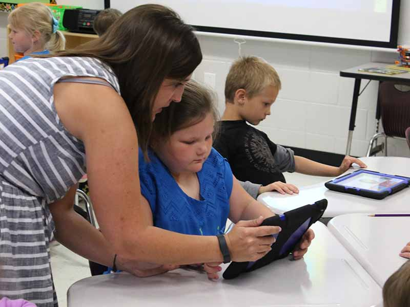 Teacher working with child with ipad