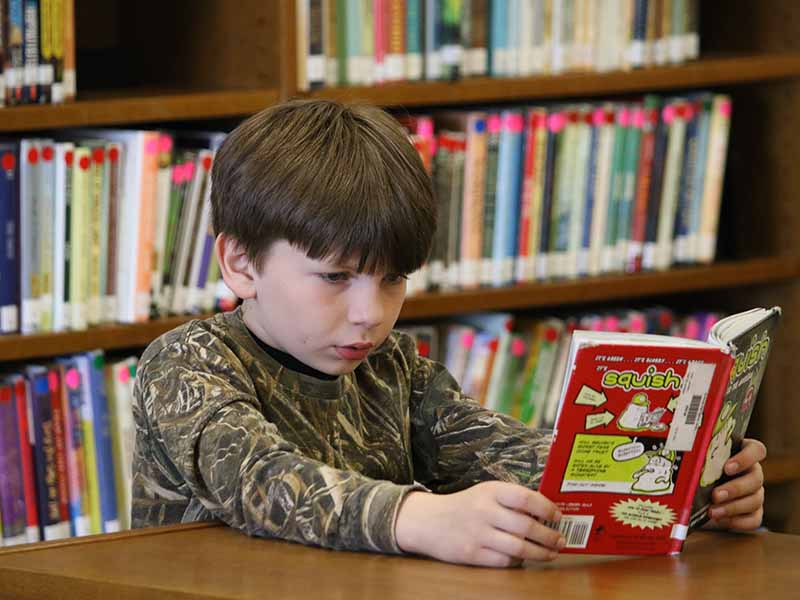 a boy student reading a book