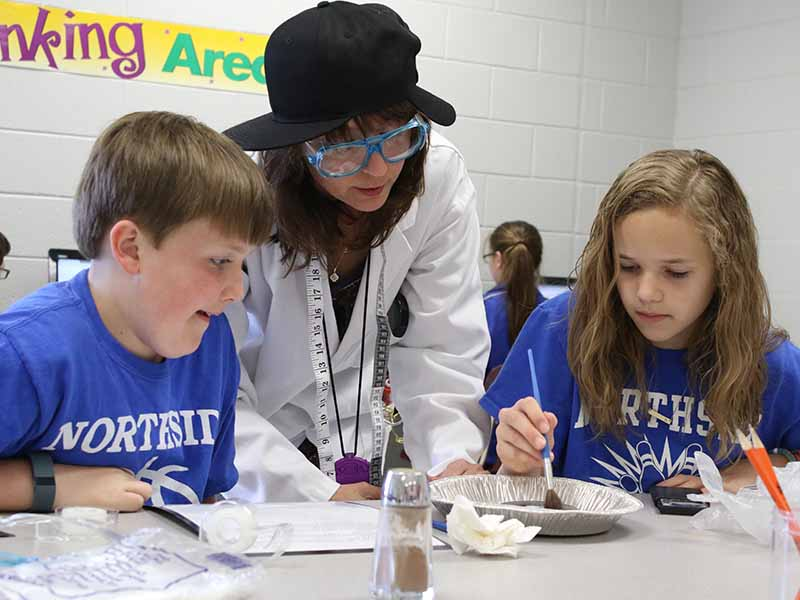 student experimenting science with teacher and another student