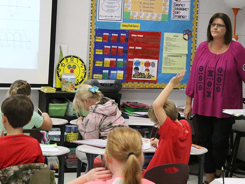 students raising their hand to answer questions